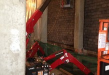 Spydercrane with manbasket next to brick wall of Chicago building