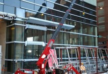 Spydercrane installing glass in building